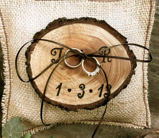 a wood burnt ring holder with twine is a nice alternative to a usual ring pillow and fits a rustic wedding