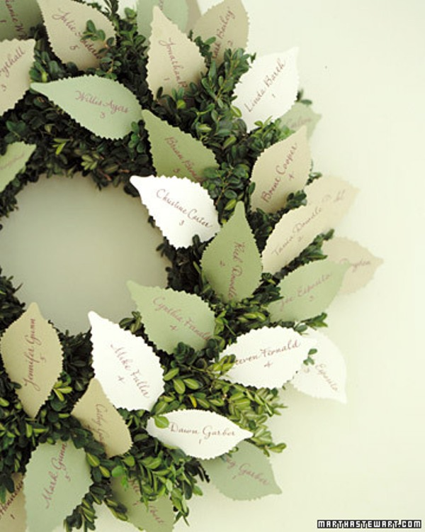a creative seating chart for a fall or winter wedding   a boxwood wreath with paper cards shaped as leaves