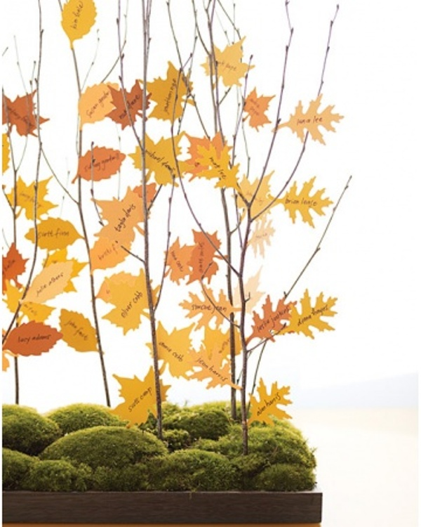 a super creative fall wedding seating chart of a moss box with branches and bright paper leaves as escort cards on them