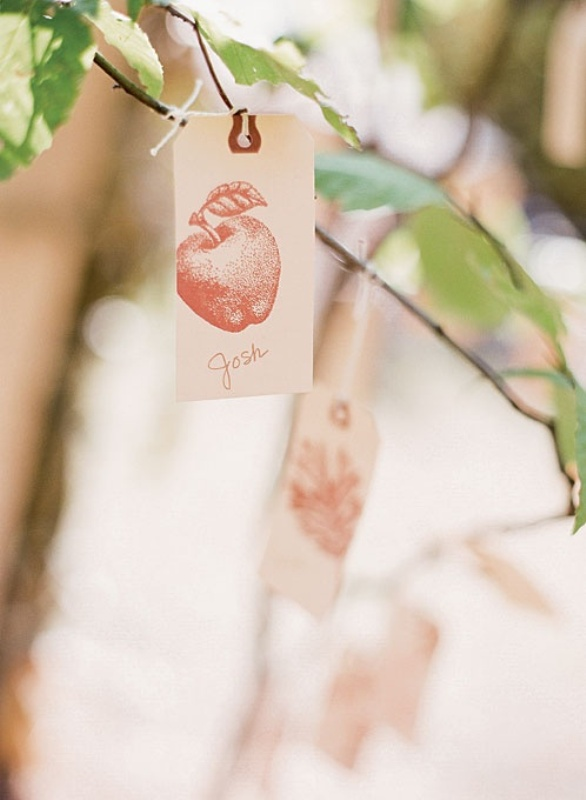 branches with leaves and vintage tags with apple prints are nice escort cards for a fall wedding