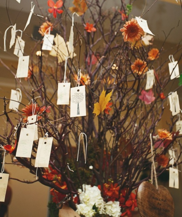 branches with bright leaves and blooms and tags with names hanging from them is a creative wedding seating chart idea