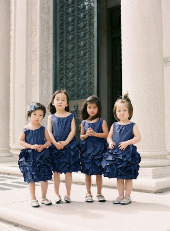 flower girls wearing navy dresses with plenty of ruffles and no sleeves look super cute and chic