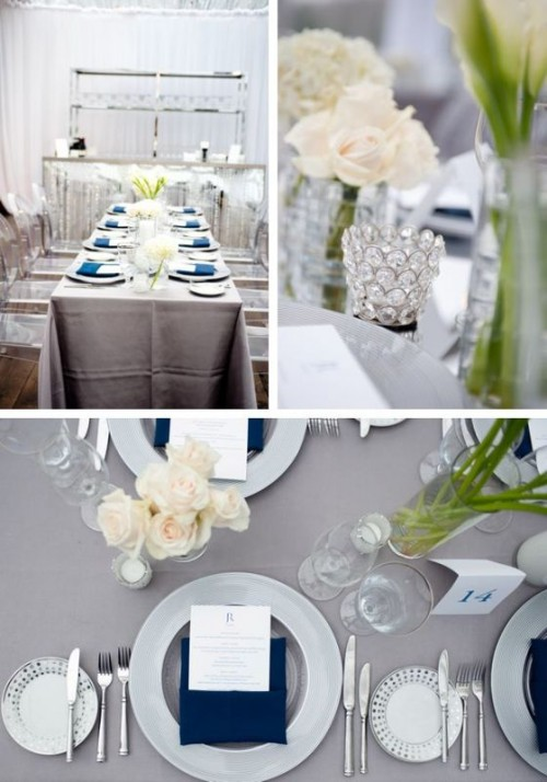 a stylish table setting with a grey tablecloth, silver tableware and navy napkins plus neutral blooms