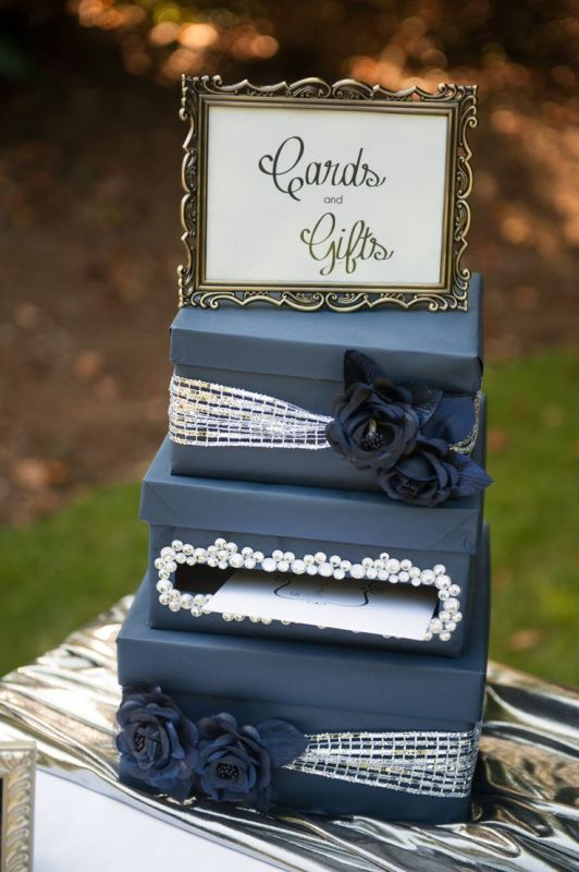 a navy and silver card box with fabric blooms, shiny ribbons and embellishments