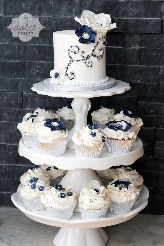 a stand with silver and navy cupcakes and a matching cake decorated with edible beads is a gorgeous idea