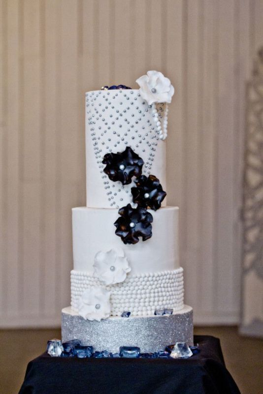a chic white, silver and navy wedding cake with sugar blooms, beads and patterns