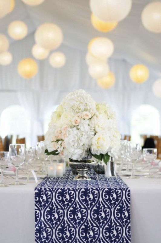 a neutral tablescape with white blooms and a catchy navy and white table runner