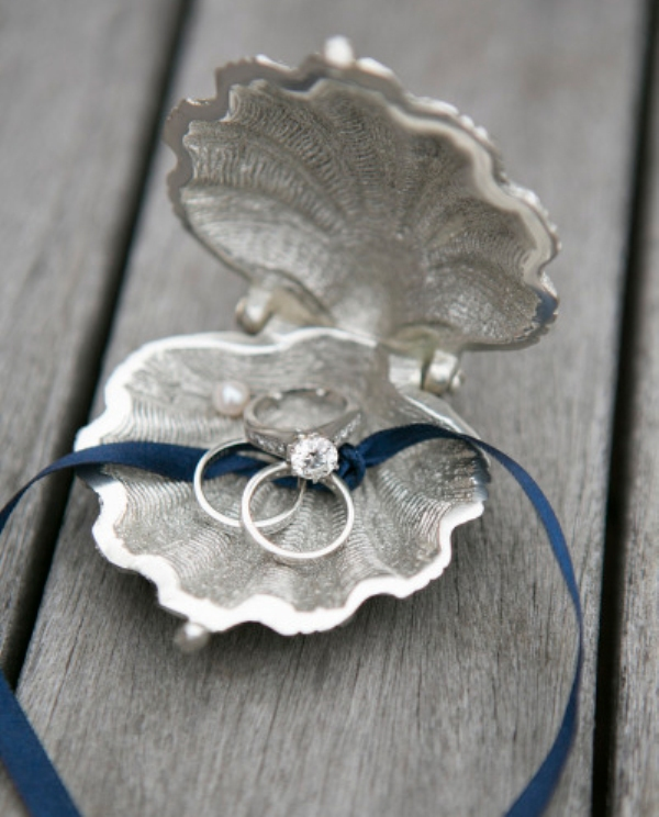 a silver shell with rings and a navy ribbon to hold them is a creative way to display your rings at the ceremony