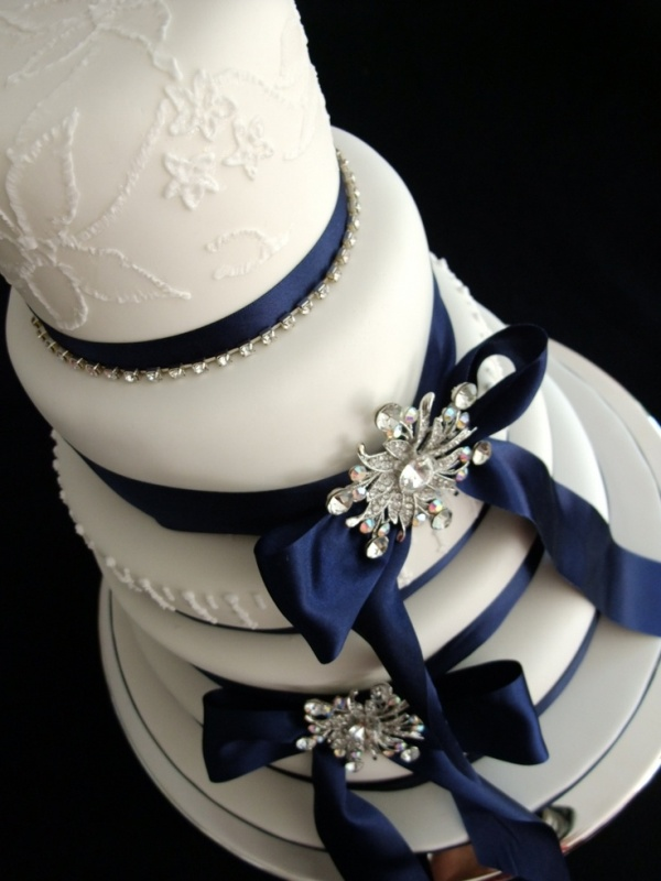 a white patterned wedding cake with navy ribbons and silver embellishments is a very elegant idea