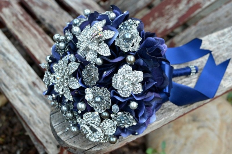 a bright wedding bouquet of navy ribbons and vintage brooches is a bold idea for a bride
