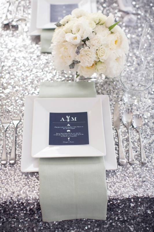 a chic tablescape with a silver sequin tablecloth, neutral blooms and a place setting with a navy menu