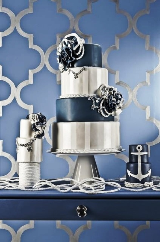 an assortment of navy and silver wedding cakes with striped and sleek tiers, sugar blooms and anchors for a nautical wedding
