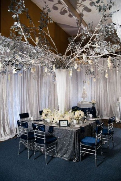 a magical setting with a large sparkling silver centerpiece, navy chairs, a silver sequin tablecloth and lots of white blooms