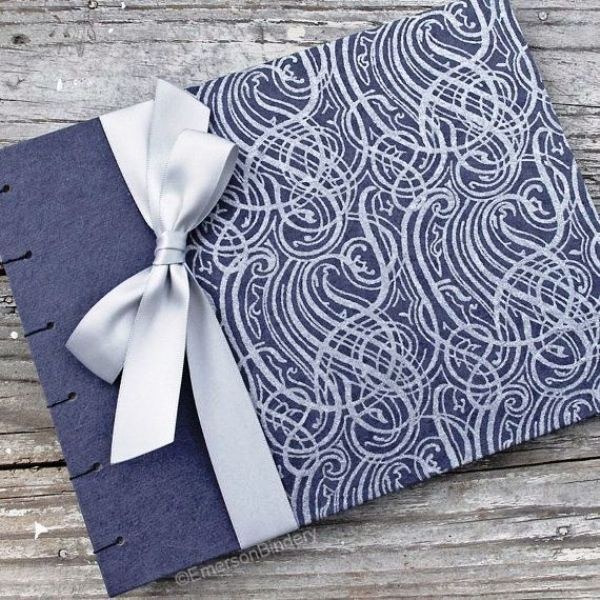 a navy and silver wedding album with a silver bow is a chic idea that matches your wedding color scheme