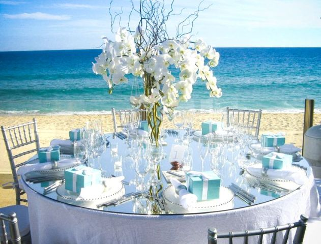 a blue and white beach wedding tablescape wiht a white orchid centerpiece, white linens, blue boxes and a gorgeous sea view