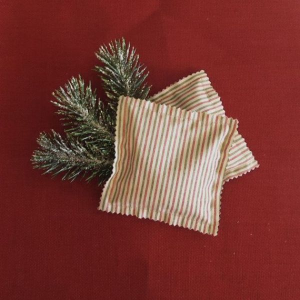 snowy fir branches in striped pockets are simple and season embracing wedding favors