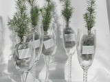 mini Christmas tree branches in fabric placed into champagne glasses are lovely and chic for a Christmas wedding