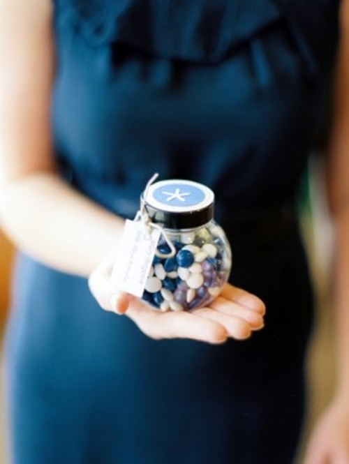 a jar with navy and white candies and a starfish sticker on top is a great idea for a beach, nautical or coastal wedding