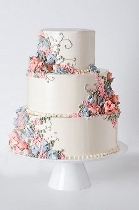 a white wedding cake with pastel blooms and greenery of sugar is a chic vintage wedding idea
