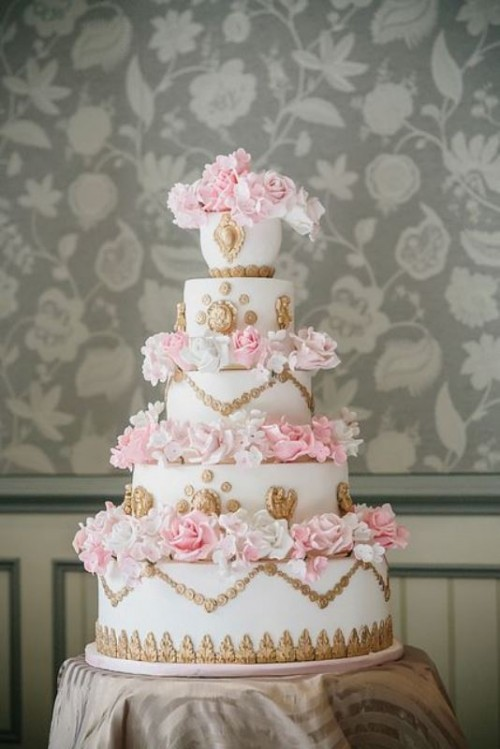 a white wedding cake with gold decor and pink sugar blooms is a chic glam idea for a vintage wedding