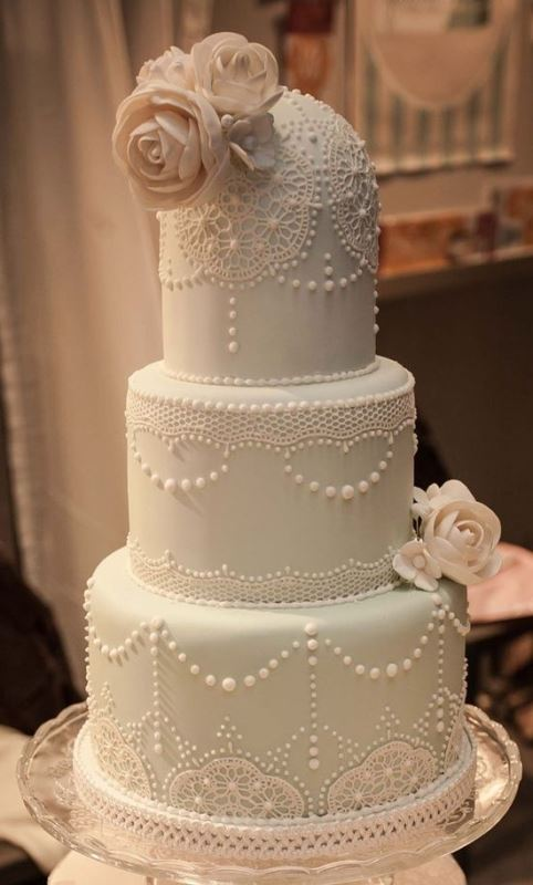 a pastel green wedding cake decorated with white lace touches, white sugar blooms and beads is a chic idea