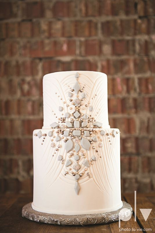 a textural white wedding cake decorated with matte and shiny beads looks really chic and beautiful