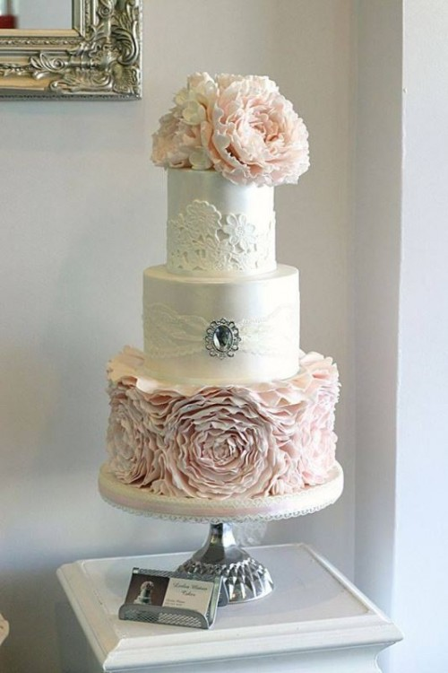 a white and blush wedding cake with a ruffle flower tier, lace and a brooch with a rhinestone plus large blush sugar blooms on top