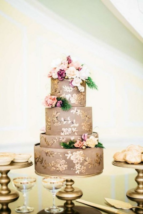 a taupe wedding cake with gold floral patterns, fresh blooms and greenery on top for a chic and refined look