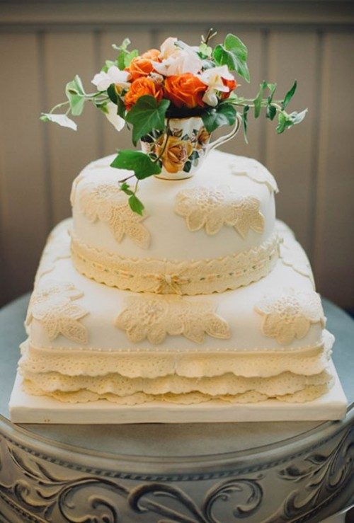 a white wedding cake with neutral lace decorations and ruffles topped with a fresh bloom arrangement in a vase