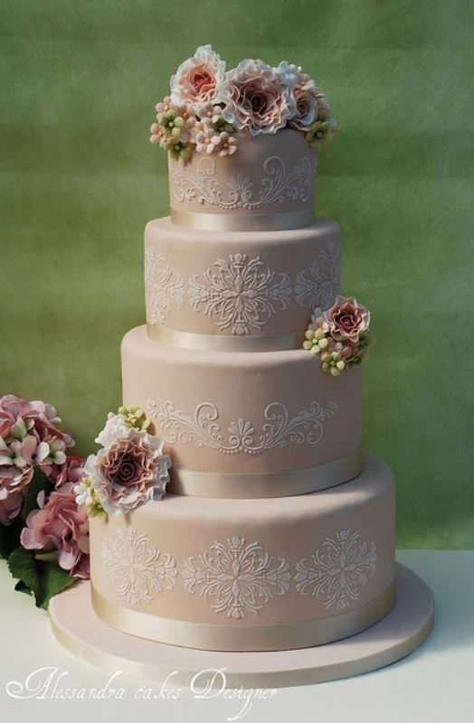 a blush wedding cake with white lace decor, creamy ribbons and some fresh blooms and greenery