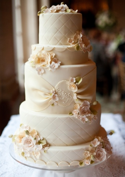 a neutral wedding cake with textural tiers and sugar blooms, monograms and sugar ribbons plus sugar greenery