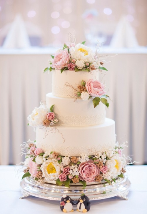 a white wedding cake with lace decor and lots of fresh blooms in pink and white and greenery