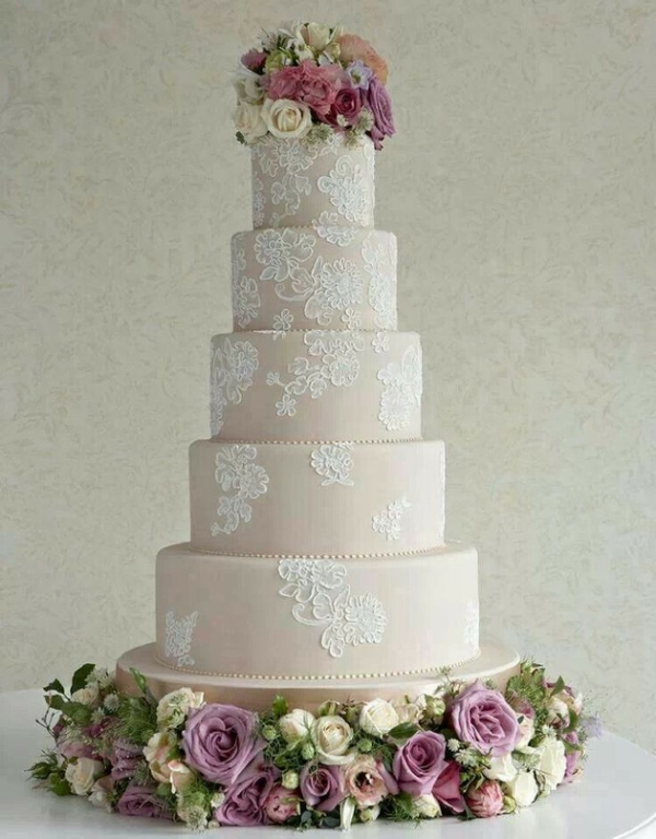 a tan wedding cake with white lace decor and pink blooms and greenery on top for a chic look