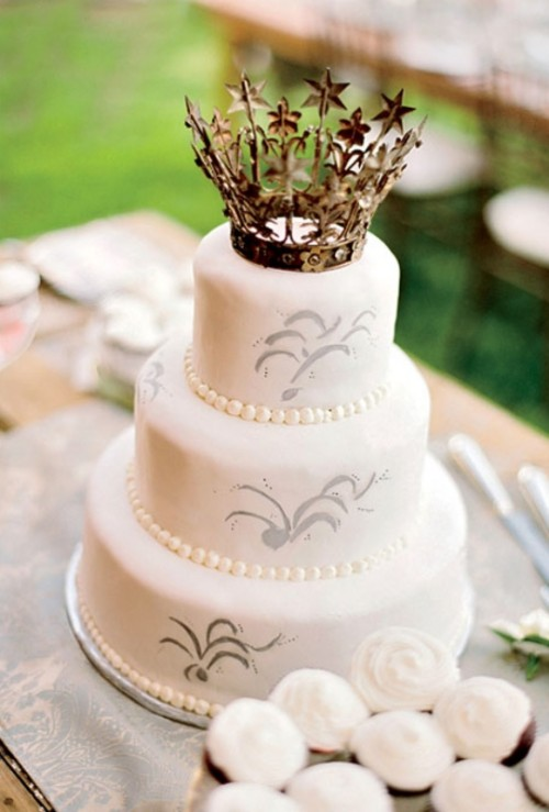 a white wedding cake with patterns and a pretty crown topper is really a royal idea