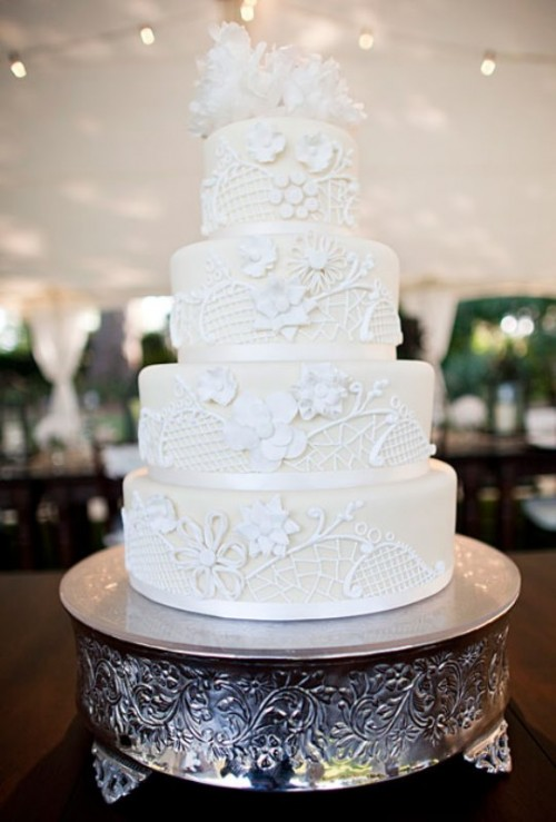 an ivory wedding cake with white lace decor and sugar blooms on top is vintage-style classics