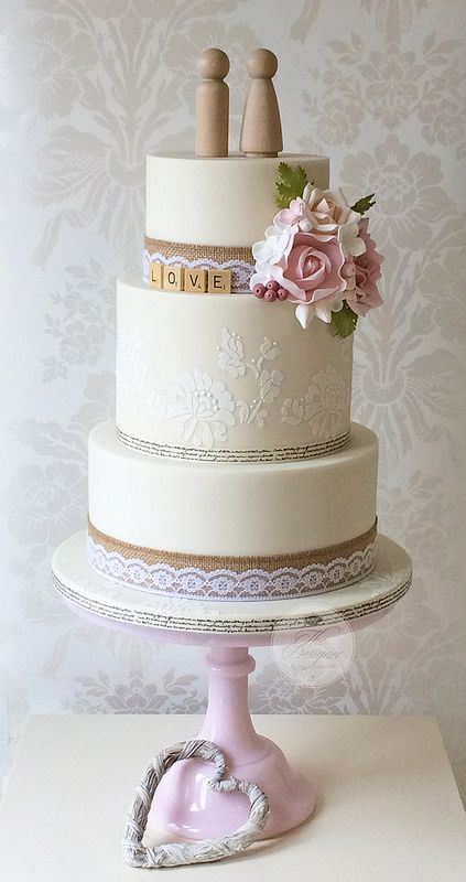 a neutral rustic vintage wedding cake with white lace, burlap ribbons, scrabble letters, pink and white sugar blooms and wooden toppers