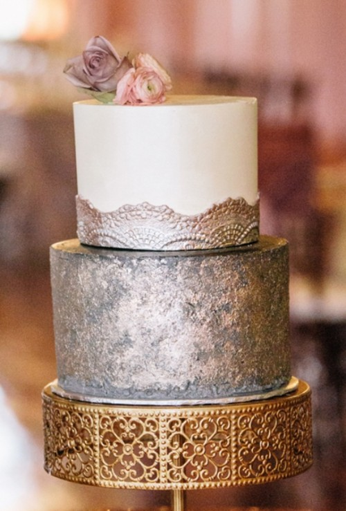 a refined wedding cake witha  copper tier and a white and copper tier plus mauve and pink blooms on top