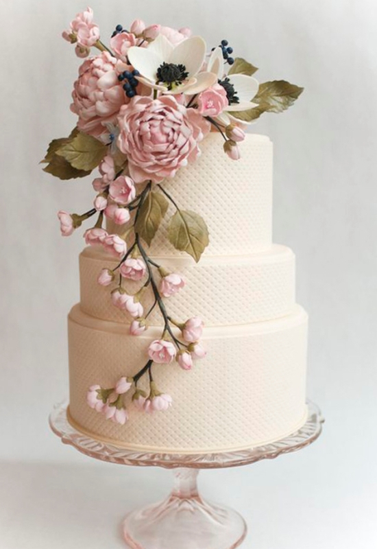a neutral textural wedding cake with pink and white sugar blooms and greenery cascading