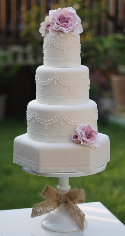 a white vintage wedding cake with patterns, pink sugar blooms on top for a refined touch