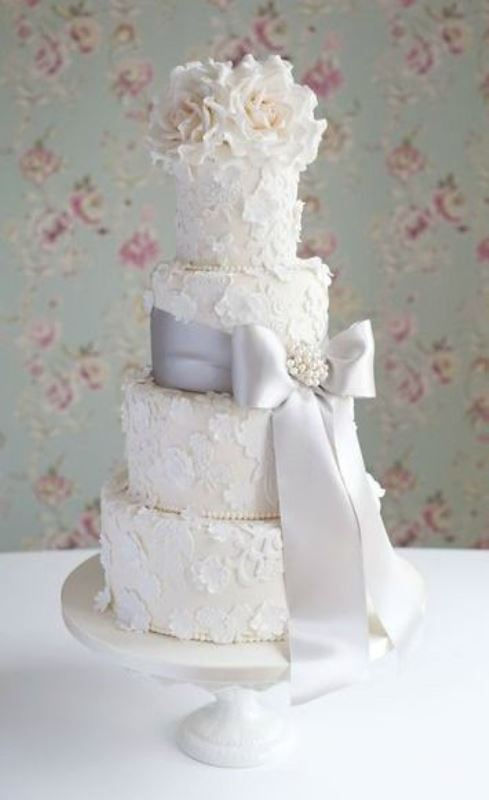 a white wedding cake with white floral lace appliques made of sugar, a lilac ribbon with a bow and a brooch and white blooms on top