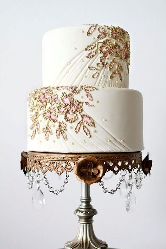 a white textural wedding cake with beading and gold and pink floral detailing is a sophisticated idea