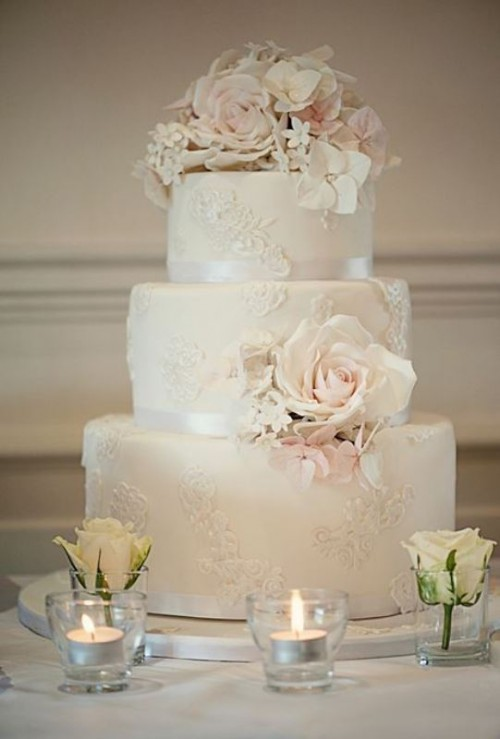 a white lace wedding cake with silk ribbons, white and blush natural blooms for a refined feel