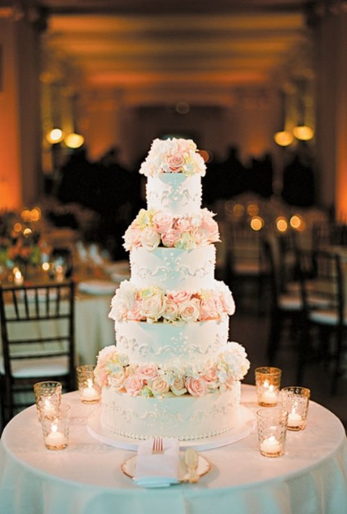 a white wedding cake with beautiful patterns and blush roses is a stylish and elegant idea