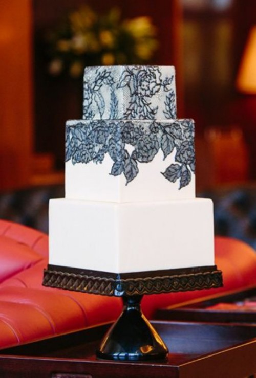 a black and white wedding cake with black lace decor is vintage-inspired, yet chic and refined