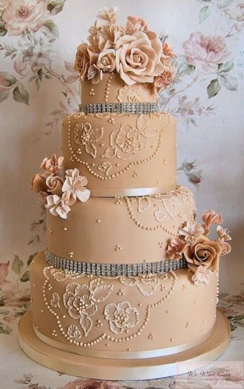 a tan wedding cake decorated with white floral patterns, ribbons, embellishments, tan sugar blooms is a glam idea