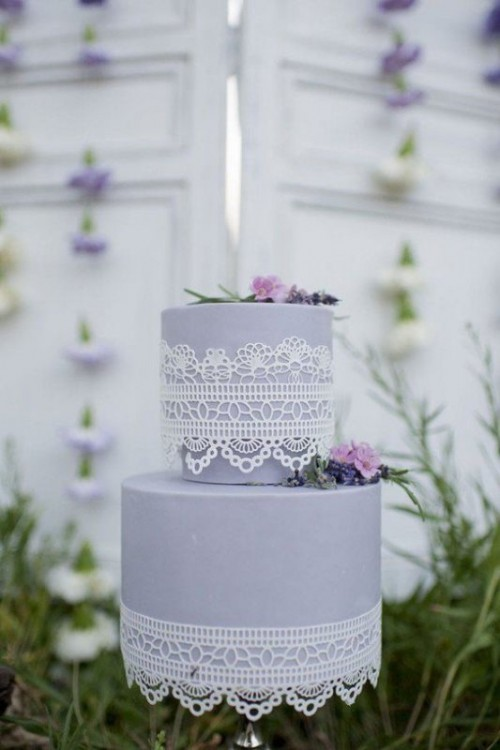 a lilac wedding cake with white lace and purple and lilac blooms and greenery is a whimsy and chic idea