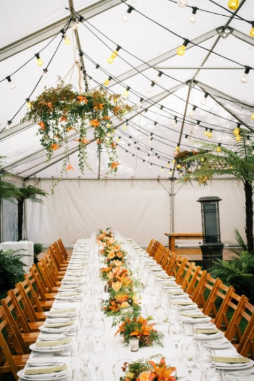 a colorful indoor spring wedding reception with lights, blooms and greenery hanging over the tables and matching blooms on the tables