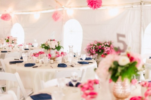 a spring wedding reception done in neutrals and spruced up with pink and navy touches, bright blooms and greenery