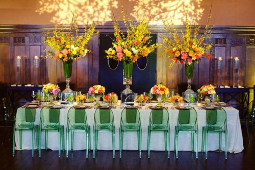 a bright spring wedding reception with colorful arrangements in tall green vases, green chairs, bright blooms