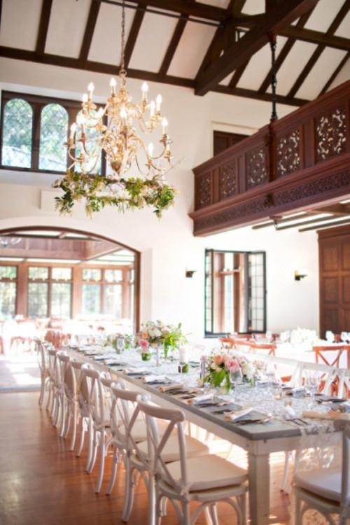 a refined indoor spring wedding reception with greenery on the chandelier, greenery and blooms on the tables and lots of natural light